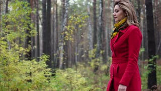 young woman in a red coat walking along an autumn park. beautiful girl enjoying a warm autumn afternoon