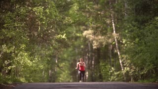 young woman jogging and rejoices achievement. the joy and taste the victory of the athlete. attractive girl is engaged in sports in a summer forest. slow motion