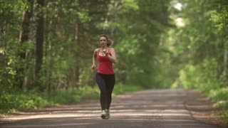 young woman Jogging in summer forest. the girl goes in for sports in the nature. the model runs towards the camera.