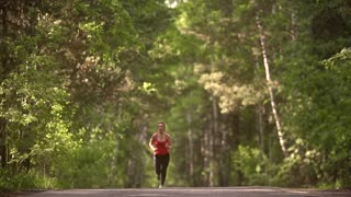 young woman Jogging in summer forest. the girl goes in for sports wireless headphones. athlete with sports wear. slow motion