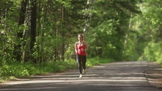 young woman Jogging in summer forest. the girl goes sports in the nature. the model runs towards the camera.