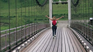 young woman traveler is anxious to meet adventures. Girl tourist with a backpack running and gaily waving her hands. slow motion