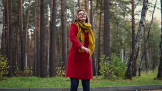 young woman walking in autumn forest. girl enjoys a warm autumn day. the girl in the red coat and scarf. slow motion