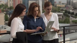 Young women in business clothes at a meeting. A group of businessmen in work in an informal setting. Business woman showing information by her colleagues on a laptop screen.