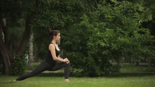 young beautiful girl doing stretching on the grass in the Park
