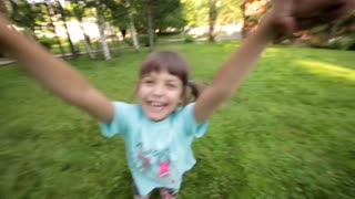 Young girl spinning around in parent's hands, Kid Smiling at Camera
