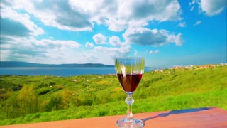 Beautiful relax background. Red wine glass on the background of panoramic view landscape. Nature, timelapse blue sky and clouds. Universal screen saver background for touristic, spa, relax themes.