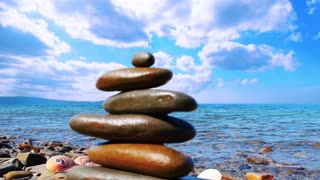 Beautiful relax background. Zen piramide from pebble stones on the background of the sea and blue sky. Timelapse blue sky, clouds. Universal screen saver background for touristic, spa, relax themes.
