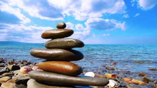 Beautiful relax background. Zen piramide from stones on the background of the sea and blue sky. Timelapse blue sky, clouds. Universal screen saver background for touristic, spa, relax themes.