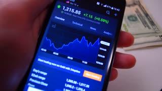 Stock market news, smartphone in hand
