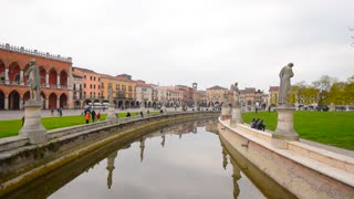Central square of old Italian city Padova, canal and antique statue. Medieval Architecture of Italy