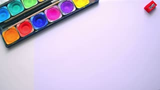 Children's creativity concept background. Get ready to drawing lesson: color paint set, paintbrush, color markers and pencils on the white table. The view from the top.
