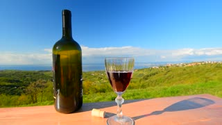 Glass and bottle of red wine. The man tastes the red wine on the background of beautiful scenery. The hill overlooking the sea