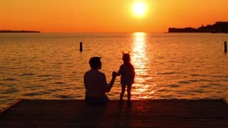 Mother and daughter sitting on the pier looking at the setting sun. Susnet on the sea. Evening sunset sky. Silhoette of woman and child on the backgrounf of sea and sunset