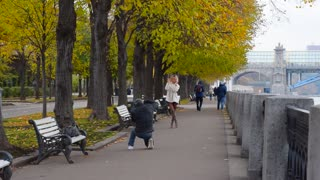 Photographer photographing a beautiful girl in autumn Park, model posing. Autumn Park with beautiful alley on the embankment of the river. Yellow leaves on the trees.