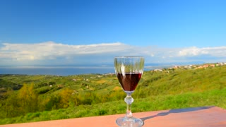 Red wine glass on the landscape background. Green hill, sea view. Relaxation background