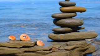 Relax background. Sea, sky, stones piramide. Three shells and a Zen pyramid of stones on the background of a sea landscape