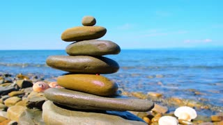 Relax background. Sea, sky, three shells and a Zen pyramid of stones on the background of a sea landscape. Ladybug crawling on a stone