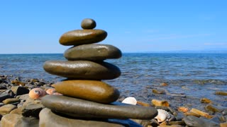 Relax background. Sea, sky, three shells and a Zen pyramid of stones on the background of a sea landscape.