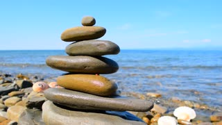 Relax background. Sea, sky, three shells and a Zen pyramid of stones on the background of a sea landscape