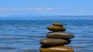 Relax background. Sea, sky, Zen pyramid frome stones. Swimmer on the SUP board in the background