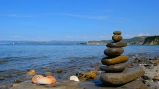 Relax background. Three shells and a Zen pyramid of stones on the background of a sea landscape and city Izola, Slovenia. Adriatic coast