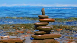 Relaxation background. Zen piramide from pebble stones on the background of the sea and blue sky, splash
