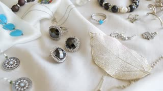 Silver jewelry, rings, bracelets and earrings at silk background.