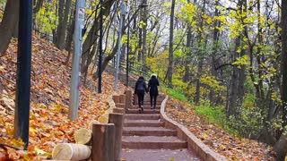 Two girls walking in the autumn Park