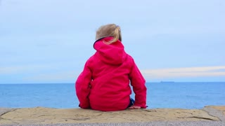 Child sitting on the sea shore looking seascape. Alone little girl 4 - 5 years old caucasian blonde in the red anorak jacket at the sea background in cloudy day, the wind rustles blond hair.