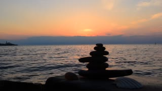 Zen symbol - pyramide from stones on the beach at the background of the sunset sea.