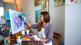 Alluring Woman Artist Sitting at Easel Painting Picture in Bright Art Studios.