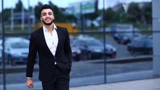 Arabic Guy in Business Center Stands Smiling Shows Yes Succes