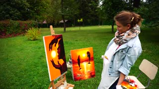Artist Woman Takes Painting From Easel and Holds, Smiles and Standing in Full Growth in Green Park Outdoors.