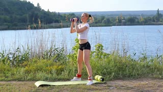Athlete female squats weighted arm legs workout outdors