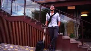 Attractive Arab Businessman Stands and Expects Meeting Near Stairs of Modern Restaurant With Travel Bag.