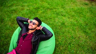 Attractive Young Arab Muslim Man Lies on Chair and Dreaming, Sipped and Resting on Background of Green Lawn in Garden Outdoors.