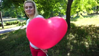 Beautiful Girl to be Expecting, Posing For Photograph and Smiles, Holding in Hand and Looks at Ballon, Stroking Tummy, Standing in Park Outdoors.