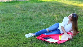 Beautiful woman sitting on a blanket and eating fast food fries. Lady with long brown hair wearing jeans and white shirt shirt enjoys the tablet on summer green grass