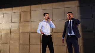 Business Team Calling Talking on Phone Near Center Office Two Men