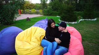 Couple in Love Sit and Talk in Multicolored Armchairs, Smiling, Hugging and Kissing Each Other Outdoors in Park.