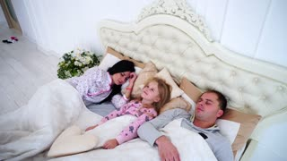 Daughter Kid is Lying in Bed and Can Not Sleep, and the Parents Are Sleeping. Girl Woke up Early