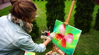 Elegant Artist Woman Completes Picture and Stands Near Easel in Park on Background of Green Grass and Bench With Art Tools Outdoors.