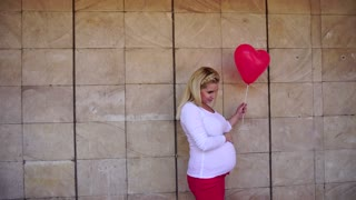 Elegant Pregnant Blonde Future Mother Looking and Poses For Photo, Smiles and Holds Beside Balloon on Background of Stone Wall in Daytime Outdoors.