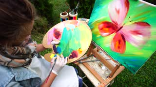 Famale Artist Mixes Oil Colors to Start Drawing Painting in Park Outdoors.
