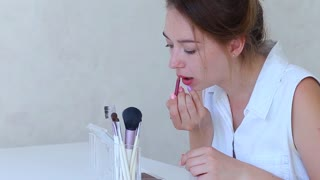 Female Young do Make up Rouge Lips With Brush For Make-Up in Girls Hand in White Room