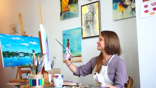Girl Artist Sits in Profile to Camera and Looking at Picture, Draws Brushstrokes and Lines on Canvas With Brush at Easel in Bright Art Class Studio.