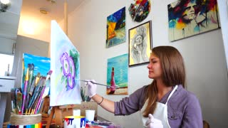 Girl Artist Sitting at Easel and Paints Brush Painting and Admires Work of Art in Light Art Studio.