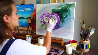 Girl Painter Sits With Back to Camera and Draws Oil Picture With Brush and Paints, Behind Easel in Art Studio.