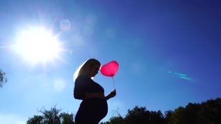 Gorgeous Pregnant Girl Holding and Raises up Balloon, Keeps on Wind and Stroking Tummy on Background of Blue Sky and Bright Sun on Open Air.